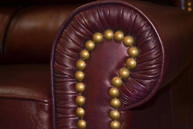 Brass upholstery tacks on armrest front