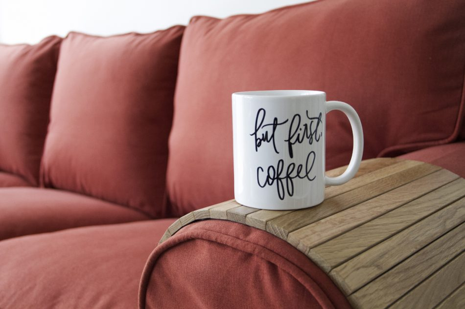 """Close-up of a mug saying """"But first, coffee"""" on top of a natural wood sofa armrest tray which rests on an Ektorp sofa in Comfort Works' custom red woollen slipcovers"""