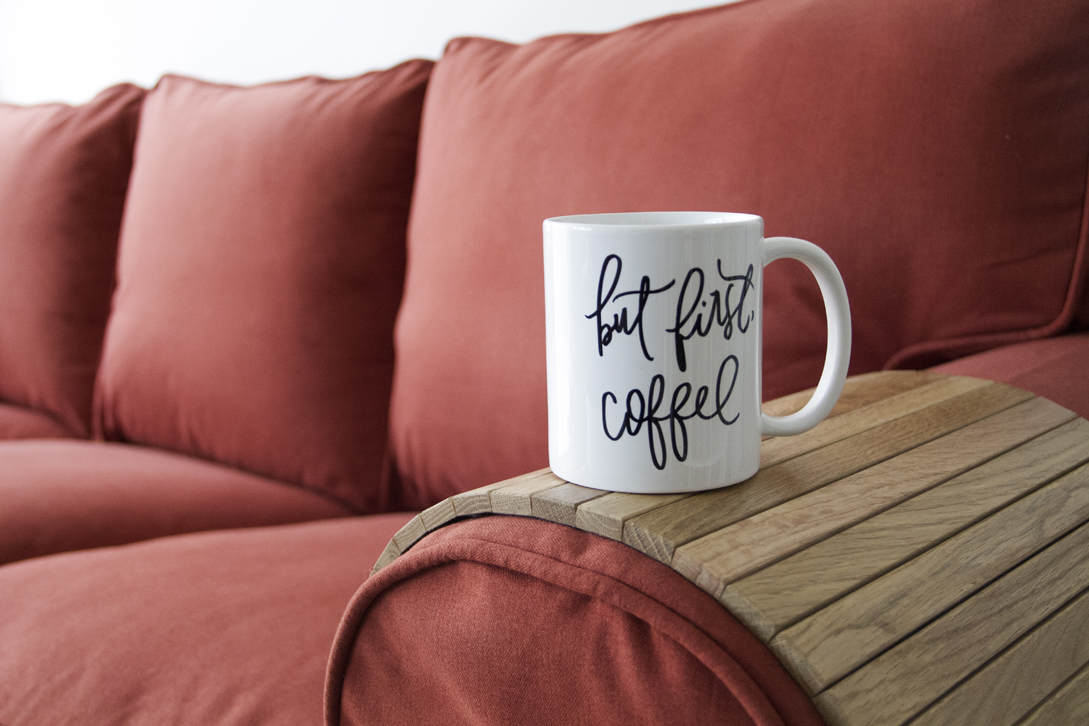 "Close-up of a mug saying ""But first, coffee"" on top of a natural wood sofa armrest tray which rests on an Ektorp sofa in Comfort Works' custom red woollen slipcovers"