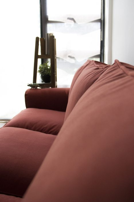 A view of the back cushions of an Ektorp sofa, covered in woollen rust-red slipcovers made by Comfort Works