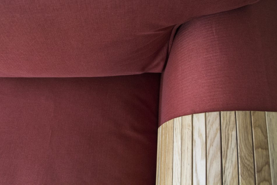 Close-up of rust-red woollen slipcovers made by Comfort Works, with a collapsible wooden sofa armrest tray in natural wood colours.