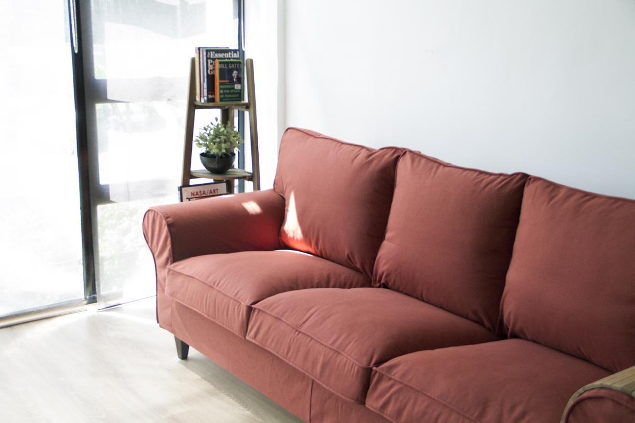 A side view of rust-red woollen custom slipcovers (made by Comfort Works) on an Ektorp sofa with decor in the background