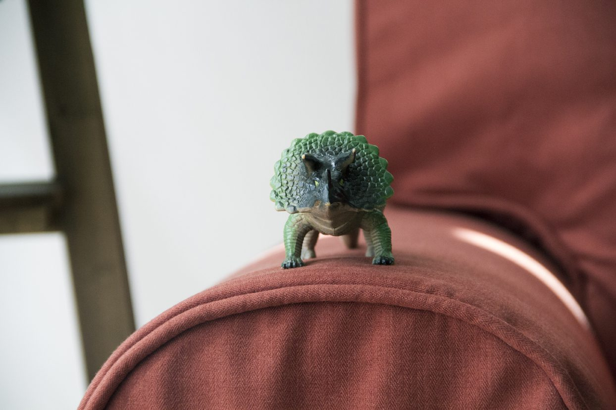A cute Triceratops on top of the armrest of an Ektorp sofa with a custom sofa cover set in Shire Rust by Comfort Works