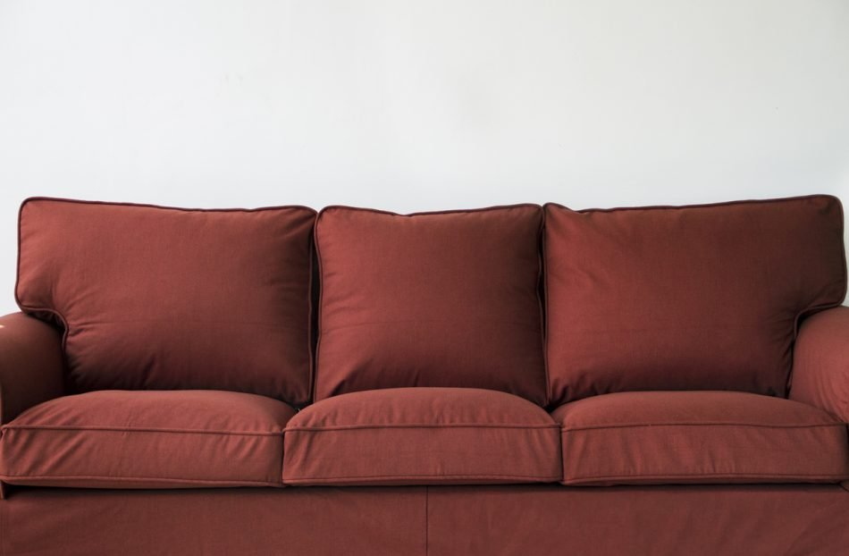 A full frontal view of IKEA's Ektorp sofa, in rust-red wool custom slipcovers made by Comfort Works