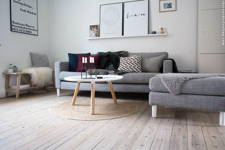 Scandinavian living room with white sofa legs and hardwood floor.
