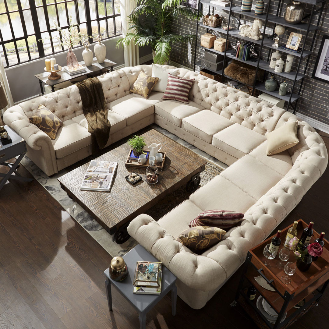 U shaped sectional in the middle of a room to fill up space and create an area for socializing.