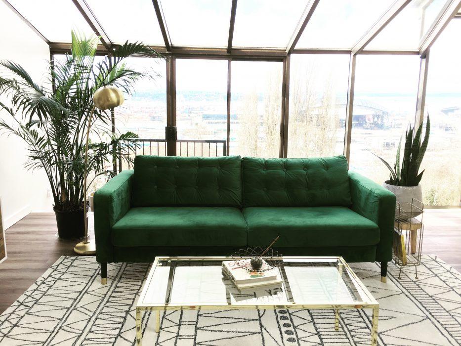 Ein sehr poliertes und sauber aussehendes Wohnzimmer. Das smaragdgrüne Samtsofa ist ein wunderbares Herzstück.