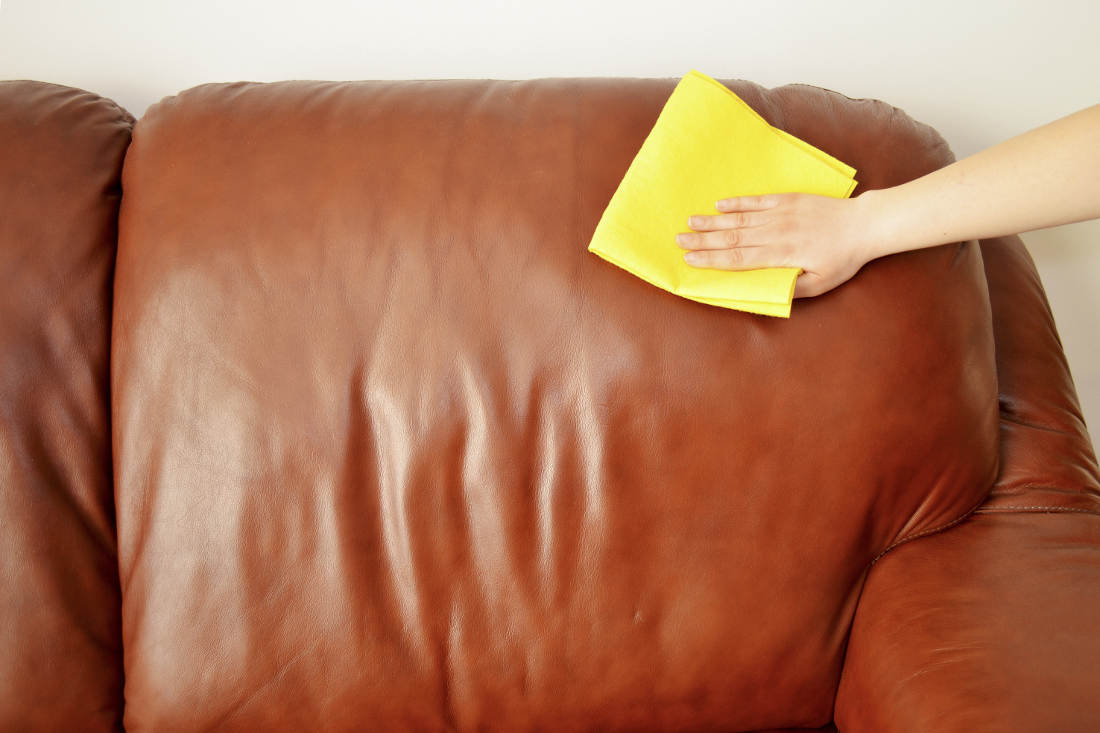 Cloth wiping down a leather couch
