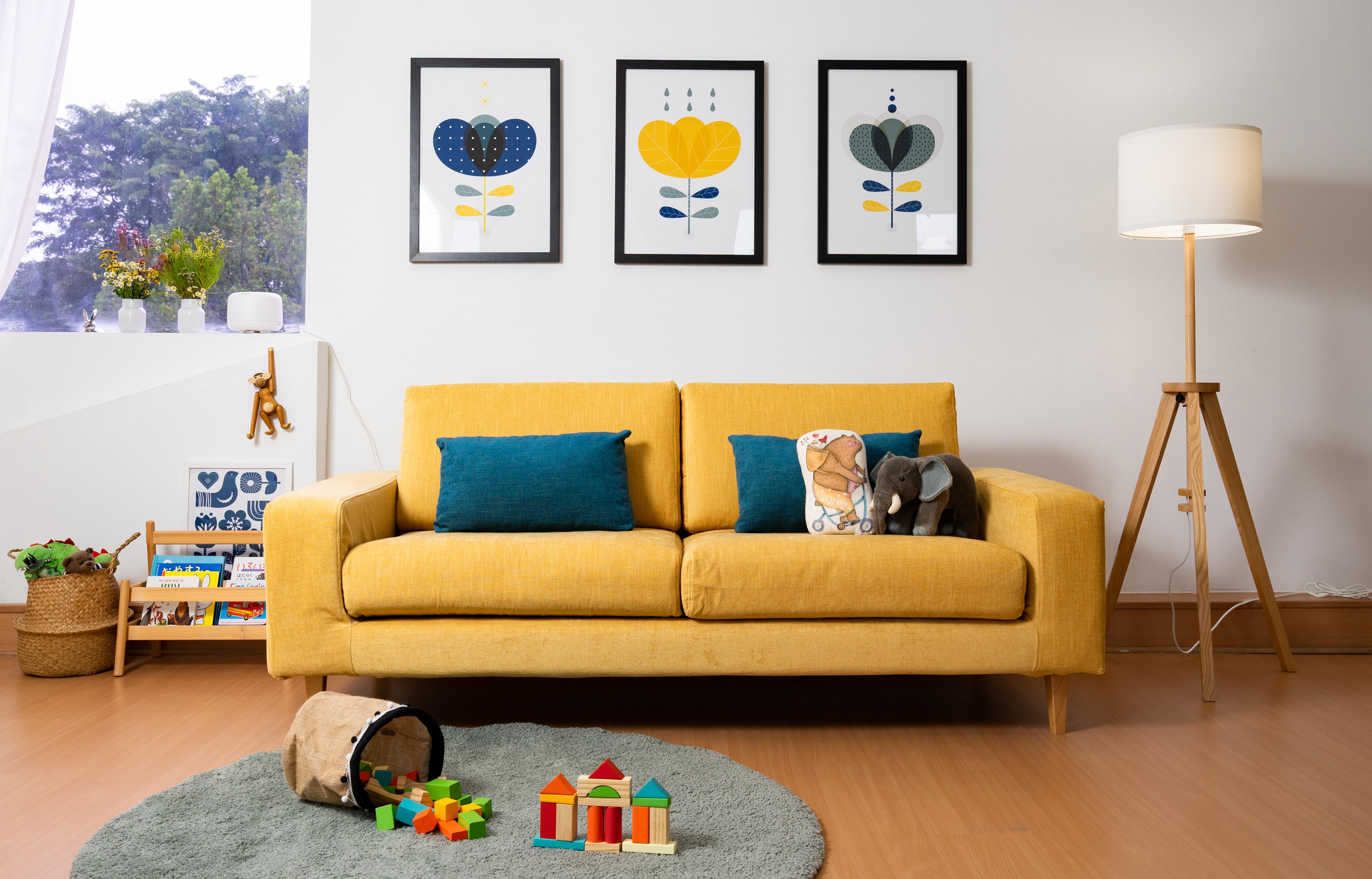 Ein gelbes Sofa mit grauem Teppich sorgt für einen strahlenden ersten Eindruck
