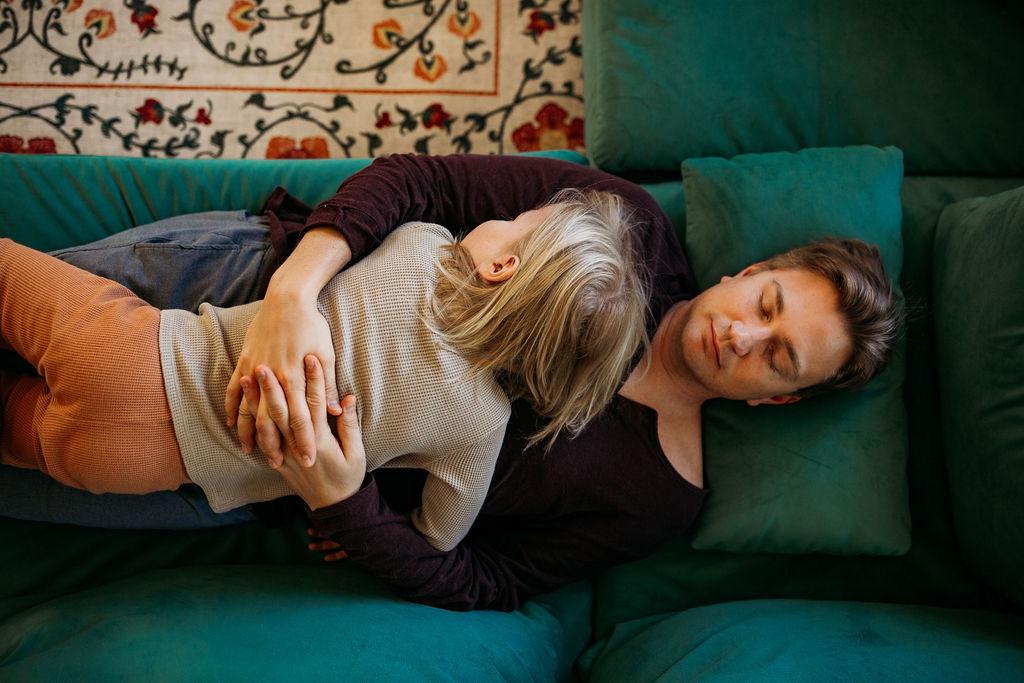 parent and child sleeping on green velvet sofa