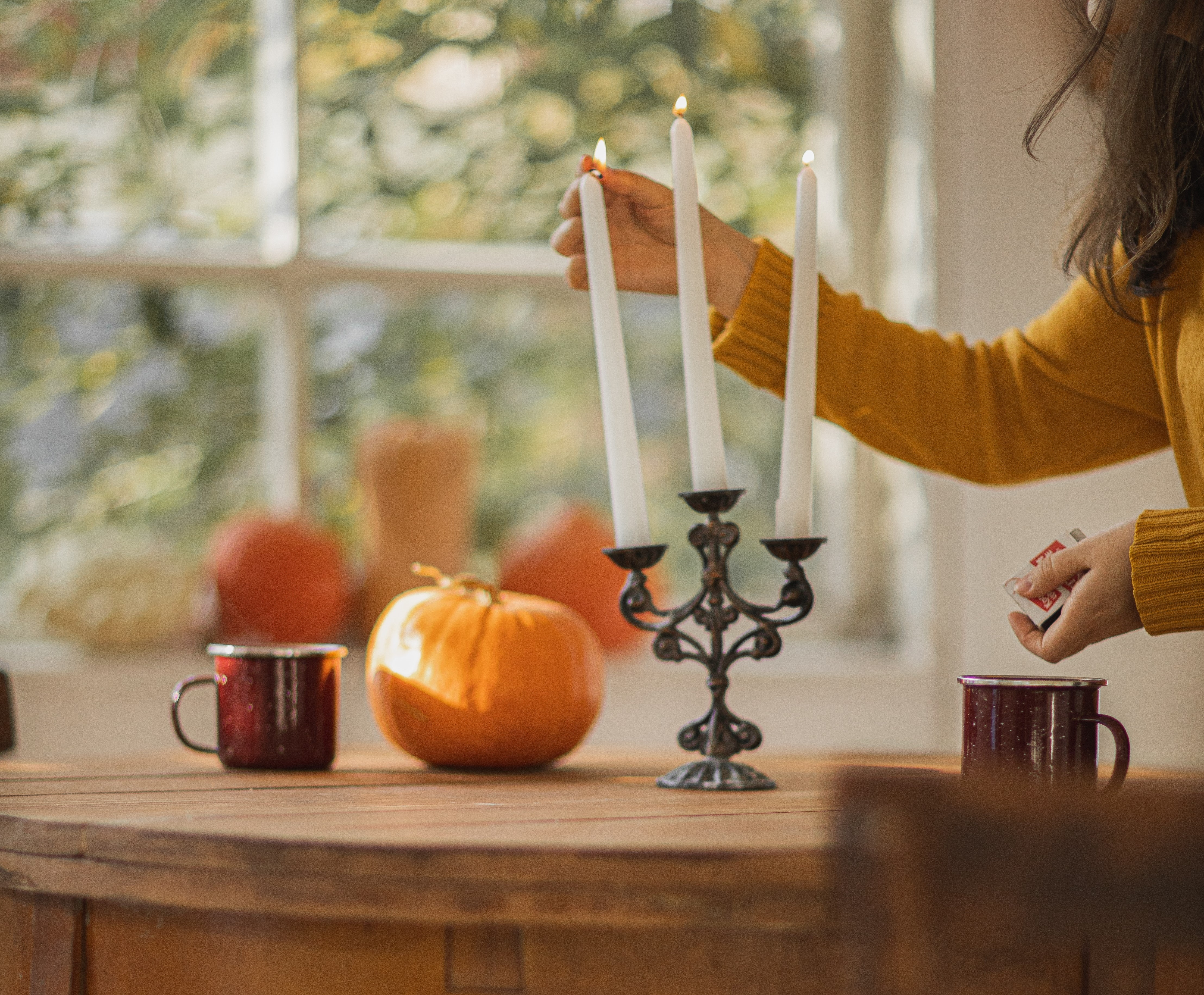 Woman decorating her home with fall candles and decoration